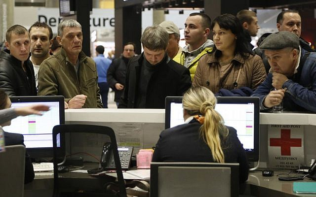 People gather at the airline information desk at of Russian airline Kogalymavia at Pulkovo airport in St.Petersburg, Russia, Saturday, Oct. 31, 2015, after a Russian airliner with 217 passengers and seven crew aboard crashed in the Sinai Peninsula. (AP Photo/Dmitry Lovetsky)