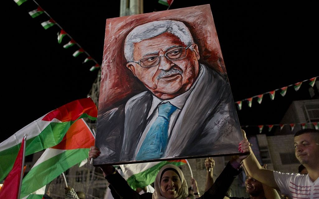 A woman carries a painting of Palestinian Authority President Mahmoud Abbas as others fly their national flags following his speech at the U.N. General Assembly shown on TV in the West Bank city of Ramallah, Wednesday, Sept. 30, 2015 (AP/Nasser Nasser)