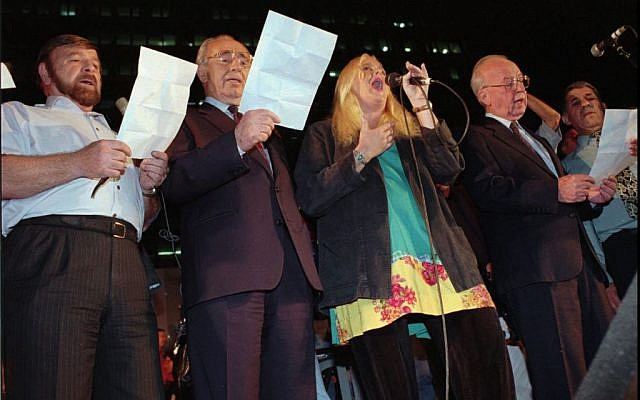 From right to left, prime minister Yitzhak Rabin, Miri Aloni, foreign minister Shimon Peres and Knesset speaker Shevah Weiss sing a 'Song for Peace' at the end of a rally in Tel Aviv on Saturday, November 4, 1995. Rabin was assassinated as he left the rally minutes later. (AP photo)