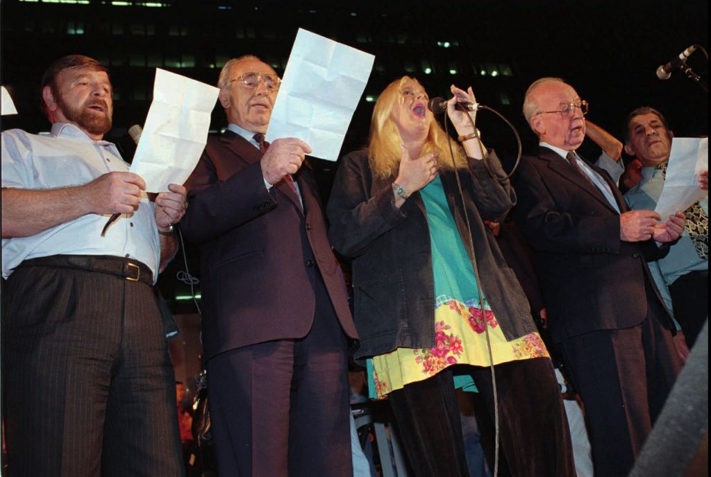 The night of the murder: (From right) Prime minister Yitzhak Rabin, Miri Aloni, foreign minister Shimon Peres and Knesset speaker Shevah Weiss sing a Song for Peace at the end of a rally in Tel Aviv on Saturday, November 4, 1995. Rabin was assassinated as he left the rally minutes later. (AP photo)