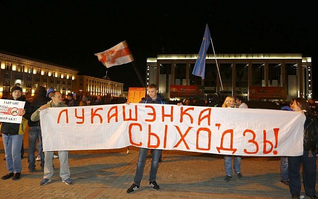"""Belarusian opposition activists rally in the city center after presidential elections in Minsk, Belarus, late Sunday, Oct. 11, 2015. The sign reads """"Lukashenko, go away!"""" (Photo by AP Photo/Sergei Grits)"""