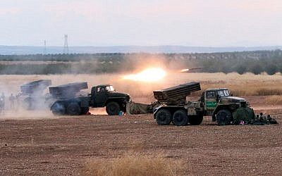 In this photo taken on Wednesday, Oct. 7, 2015, Syrian army rocket launchers fire near the village of Morek in Syria. (AP Photo/Alexander Kots, Komsomolskaya Pravda, Photo via AP)