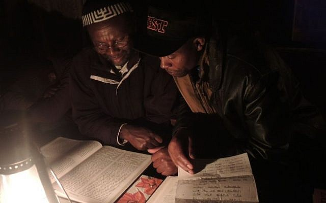Yosef Njogu, left, and Asher Muiru, who is part of a small community of Jews in the village of Moro, about four hours away, look over a tikkun. A page that fell out of the book when they opened it was a trop [chanting melody] sheet I used for my Bat Mitzvah 17 years ago. (Melanie Lidman/Times of Israel)