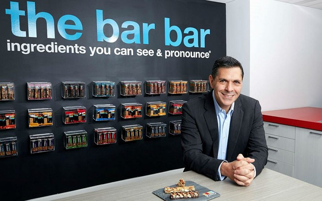 Daniel Lubetzky in the kitchen area of the Kind Snacks office in New York City with the many flavors of his company's bars on display. (Poon Watchara-Amhaiwan/via JTA)