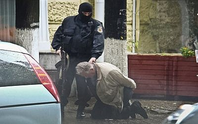 Teodor Chetrus is detained by a police officer in Chisinau, Moldova during a uranium-235 sting operation, June 27, 2011. (Moldova Police via AP)