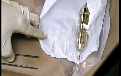An investigator looks at a vial containing cesium-135 on the driver's seat of Valentin Grossu's car following his arrest in Chisinau, Moldova, In this February 19, 2015. (Moldova Police via AP)