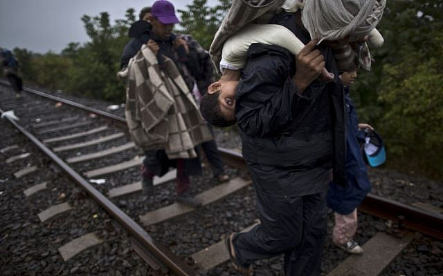 A 10-year-old Syrian migrant is carried on the back of her father as they make their way along a railway track after crossing the Serbian-Hungarian border near Roszke, southern Hungary. (AP/Muhammed Muheisen)