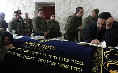Aman prays as he is surrounded by Israeli soldiers in Joseph's Tomb in the West Bank city of Nablus, December 28, 2010. (Kobi Gideon/Flash90)