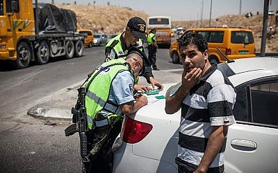 Illustrative: Police examining Palestinians on their way to Ramallah near the Adam Junction. (Noam Moskowitz/Flash90)