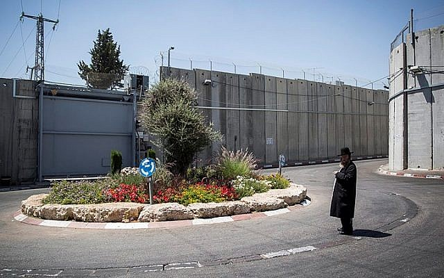 Illustrative: An Ultra Orthodox Jewish man stands by the intersection at the entrance to the Jewish religious site of Rachel's Tomb, surrounded by the Separation Wall, near Bethlehem, on June 26, 2014. (Hadas Parush/Flash90)