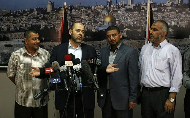 Senior Hamas official Moussa Abu Marzouk (second from left) speaks to media at the Rafah crossing in the southern Gaza Strip after negotiations in Cairo, August 28, 2014. (Abed Rahim Khatib/Flash90)