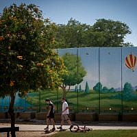 Israeli children play near a colorfully painted  concrete protective shelter in the kibbutz of Nahal Oz. July 6, 2015. (Miriam Alster/FLASH90)