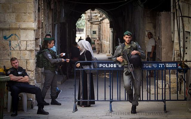 An Israeli border police woman checks the ID papers of a Muslim woman leaving the Al-Aqsa mosque compound in Jerusalem's Old City on September 17, 2015. (Miriam Alster/Flash90)
