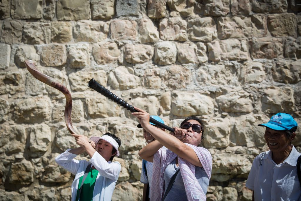 Chinese tourists blow the shofar at the Jaffa Gate to Jerusalem's Old City on September 29, 2015. (Hadas Parush/Flash90)