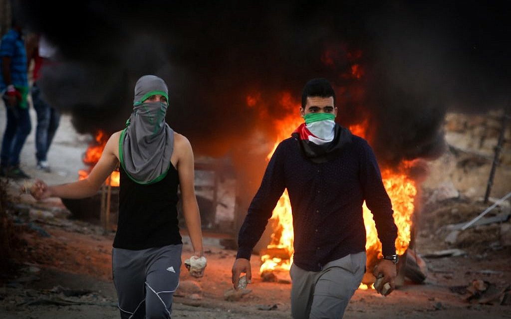 Palestinian protesters throw stones and burn tires during clashes with Israeli security forces close to the Israeli checkpoint of Hizma in the West Bank, September 30, 2015 (Flash90)