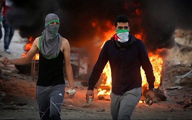 Palestinian protesters throw stones and burn tires during clashes with Israeli security forces over the Temple Mount, close to the Hezma checkpoint in the West Bank, September 30, 2015. (Flash90)