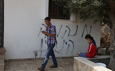 "Palestinians outside a home where alleged Jewish extremists daubed Hebrew graffiti, which reads ""revenge, Henkin"", and set fire to a car, in Bitilu village near the West Bank city of Ramallah on October 2, 2015. (Flash90)"