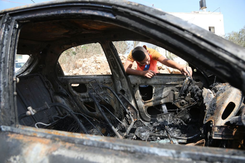 A Palestinian boy looks at a car which residents said was torched by alleged Jewish extremists, in Bitilu village near the West Bank city of Ramallah on October 2, 2015. (Photo by Flash90)
