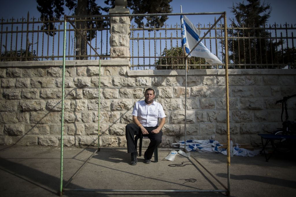 "Yossi Dagan, head of the Samaria Regional Council, sits at a Sukka outside the Prime Minister's Residence in Jerusalem on October 2, 2015. Dagan announced Friday that he was starting a hunger strike protest in the wake of the murder of Israeli couple, Naama and Eitam Henkin, to demand what he called ""an appropriate response"" from Prime Minister Benjamin Netanyahu (Photo by Yonatan Sindel/Flash90)"