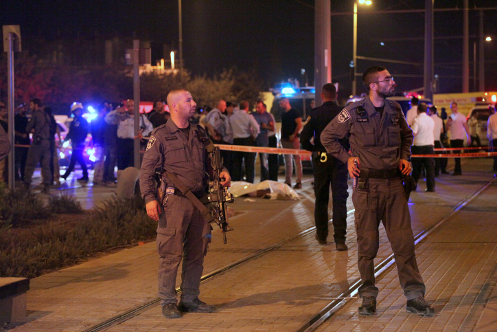 Israeli police stand near the body of a Palestinian terrorist who stabbed an 15-year-old Israeli outside Jerusalem''s Old City on October 4, 2015. (Flash90)