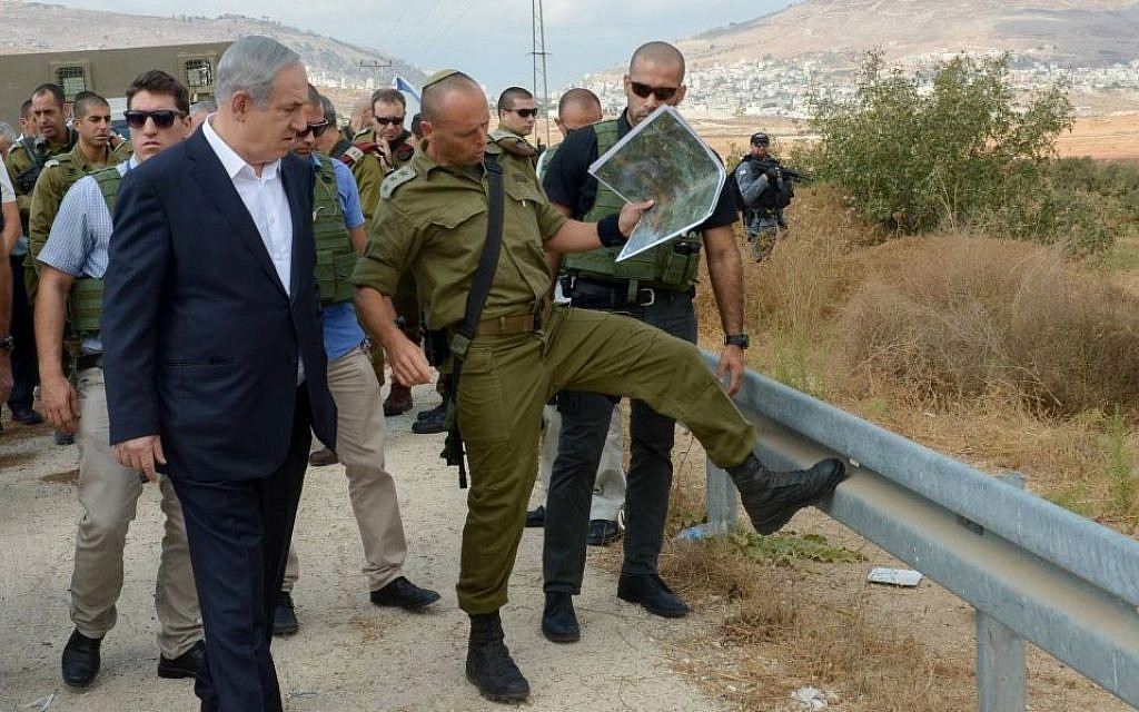 Benjamin Netanyahu with army officials at the site of a terror attack in the West Bank on October 6, 2015. Amos Ben Gershom/GPO)