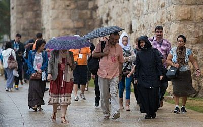 People walking by Jaffa Gate near the Tower of David in Jerusalem's Old City during the first rain of the season, October 7, 2015. (Yonatan Sindel/Flash90)