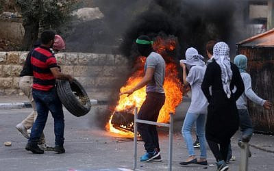 Dozens of Palestinian protesters burn tires and throw stones at Israeli troops during clashes near the West Bank city of Ramallah and elsewhere on Thursday. October 08, 2015. (FLASH90)