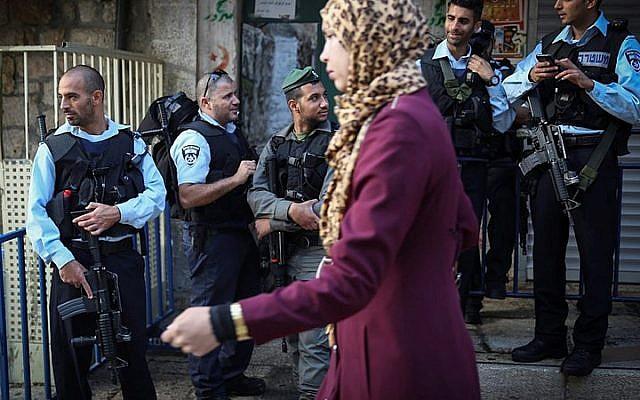 A Palestinian woman walks past Israeli policemen on the Via Dolorosa street in the Muslim Quarter in Jerusalem's Old City on October 8, 2015. (Hadas Parush/Flash90)