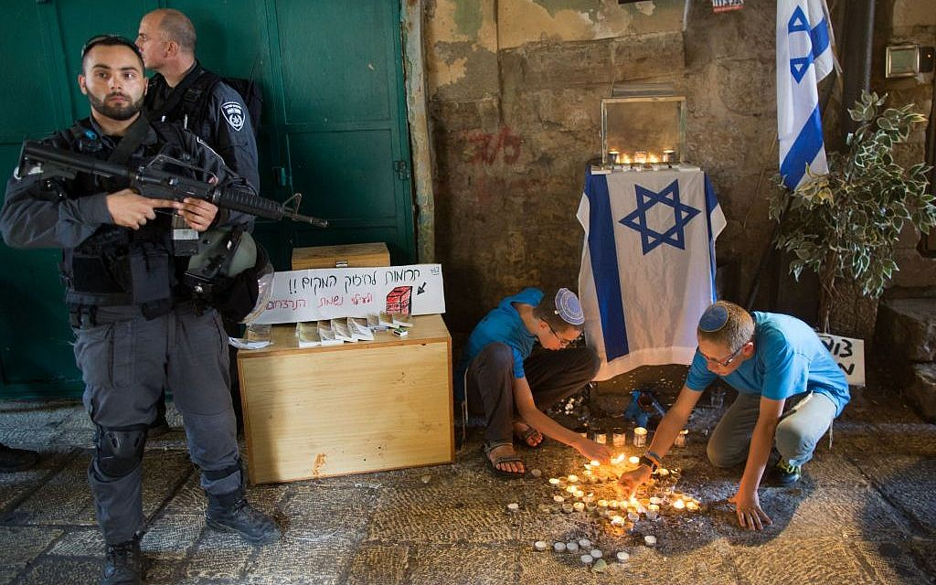 Jewish teenagers light candles in the shape of a star of David at the site of last week's stabbing attack in the Muslim Quarter in the Old City of Jerusalem, October 8, 2015 (Yonatan Sindel/Flash90)