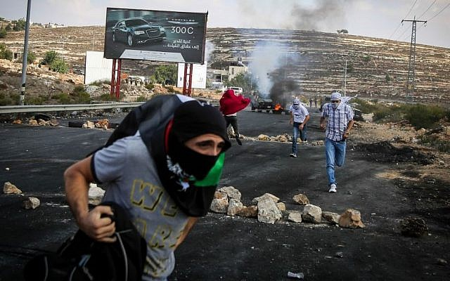 Illustrative photo of Palestinian protesters hurling stones towards Israeli troops during clashes by the Jewish settlement of Bet El, near the West Bank city of Ramallah October 10, 2015. (FLASH90)