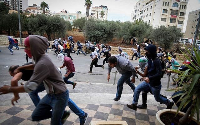 Palestinian protesters hurling stones clash with Israeli troops (not seen) during riots by the Jewish settlement of Bet El, near the West Bank city of Ramallah, October 10, 2015 (Flash90)