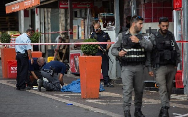 Police standing near the body of a Palestinian terrorist at the scene where a stabbing attack took place near Damascus Gate in the Old City of Jerusalem on October 10, 2015 (Yonatan Sindel/Flash90)