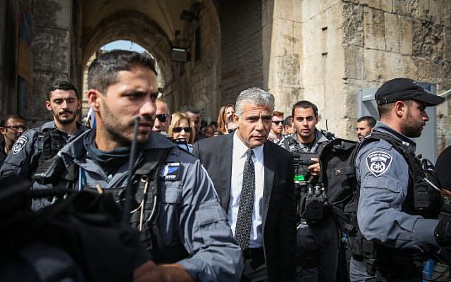 Yesh Atid party leader Yair Lapid surrounded by policemen during a visit to the Lion's Gate in Jerusalem's Old City, the site of an attempted stabbing attack on October 12, 2015. (Hadas Parush/Flash90)