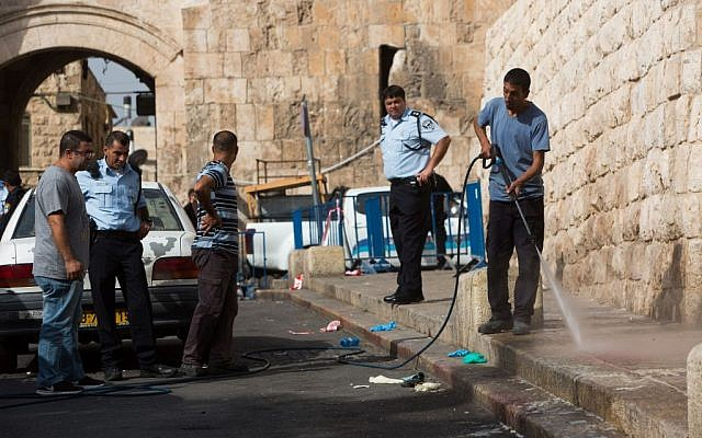 A man cleans the scene after an attempted stabbing of a police officer outside Lions' Gate in the Old City of Jerusalem on October 12, 2015. (Photo by Yonatan Sindel/Flash90)