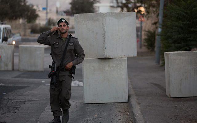 An Israeli Border Police guard seen at the road block set up at the entrance to the East Jerusalem neighborhood of Jabel Mukaber, on October 14, 2015. (Yonatan Sindel/Flash90)