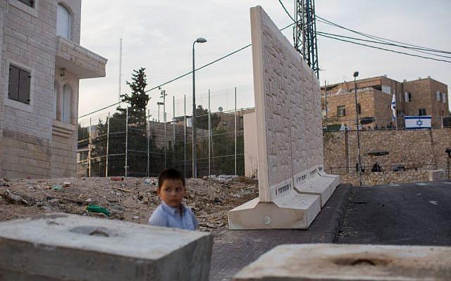 A Palestinian child stands near concrete walls in the East Jerusalem neighborhood of Jabel Mukaber, October 18, 2015. (Yonatan Sindel/Flash90)