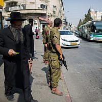 Israeli soldiers guard at a bus stop in the ultra-Orthodox neighborhood of Mea Shearim in Jerusalem on October 19, 2015. (Yonatan Sindel/Flash90)
