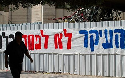 Jerusalemites walk by a large sign reading 'The main thing is not to fear at all.' posted in downtown Jerusalem following the recent wave of terror attacks (Nati Shohat/Flash 90)