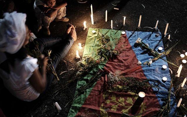 Mourners light candles on an Eritrean flag as they eulogized Haftom Zarhum on October 21, 2015. (Tomer Neuberg/Flash90)
