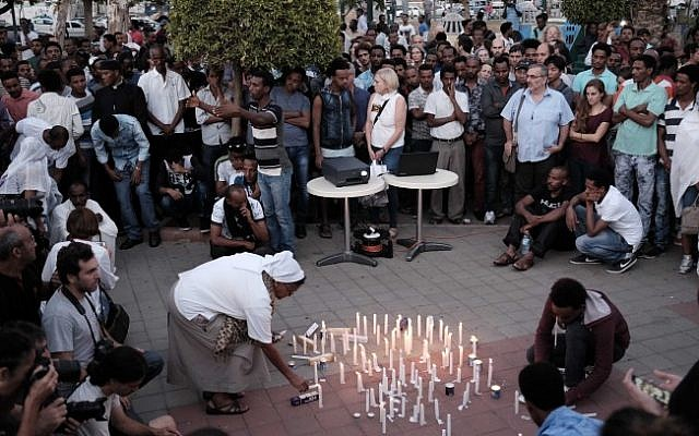 Sr Azezet Kidane, a Comboni Sister originally from Eritrea, lights a memorial candle for Haftom Zarhum. About 200 Israelis attended to show support. (Tomer Neuberg/Flash90)