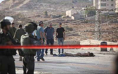 Israeli security forces seen near the body of the Palestinian terrorist after he stabbed and severely wounded an Israeli soldier near the Adam junction, north of Jerusalem. The stabber was shot and killed by security forces at the scene, the IDF said. October 21, 2015. (Yonatan Sindel/FLASH90)