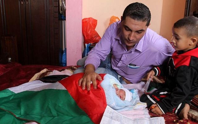 A Palestinian baby boy named 'Knife of Jerusalem' is wrapped in a Palestinian flag and displayed for members of the media, at his family's home in Rafah, southern Gaza, on October 24, 2015. (Abed Rahim Khatib/Flash90)
