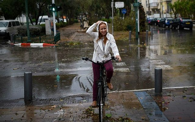 MK Stav Shaffir (Zionist Union) rides her bicycle through heavy rain and strong winds as a thunderstorm hits Tel Aviv, October 25, 2015. (Ben Kelmer/Flash90)