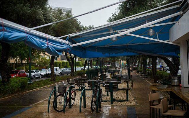 Empty chairs at an outdoor cafe on Tel Aviv's Ben Gurion Boulevard as a thunderstorm hits Tel Aviv, October 25, 2015. (Ben Kelmer/Flash90)