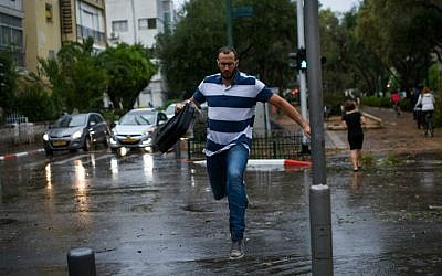 File: A man jumps over a rain puddle as a thunderstorm hits Tel Aviv, October 25, 2015. (Ben Kelmer/Flash90)