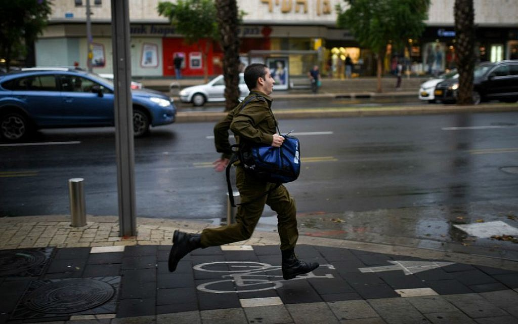 An Israeli soldier runs in heavy rains and strong winds as a thunderstorm hits Tel Aviv, October 25, 2015. (Ben Kelmer/Flash90)