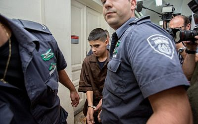 Ahmed Manasra, a 13-year-old Palestinian who stabbed two Israelis in an attack, is seen surrounded by guards at the Jerusalem Magistrate's Court on October 25, 2015. (Yonatan Sindel/Flash90)
