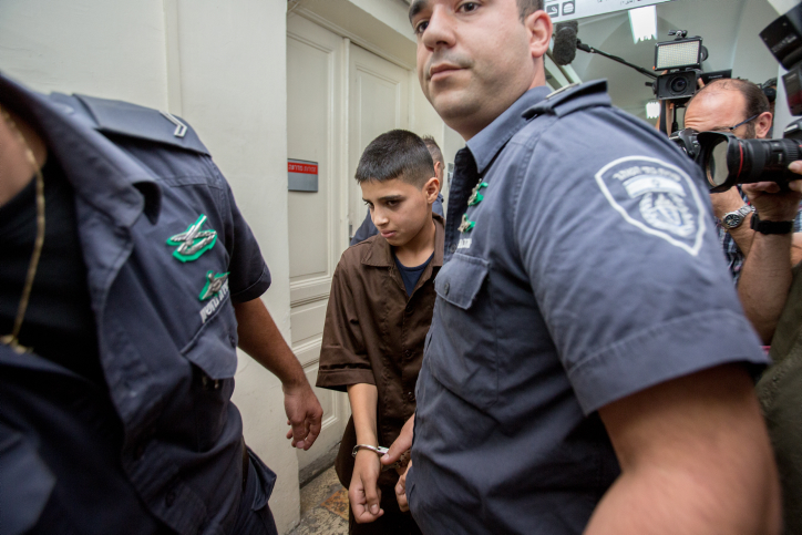 Palestinian 13-year-old Ahmed Manasra seen surrounded by guards at the Jerusalem Magistrate's Court on October 25, 2015. (Yonatan Sindel/Flash90)