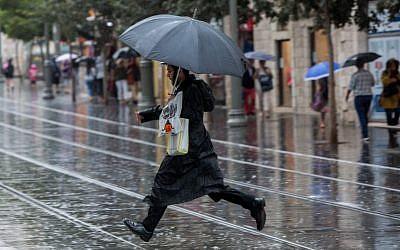 An ultra-Orthodox Jewish man holds an umbrella on Jaffa Street, downtown Jerusalem on a rainy day, October 25, 2015. (Yonatan Sindel/Flash90)