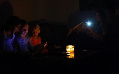 An Israeli family sits in the darkness in their home, near the Israeli town of Netanya, a day after a powerful rainstorm hit Israel on October 15, 2015, downing trees and hundreds of power lines. (Chen Leopold/FLASH90)